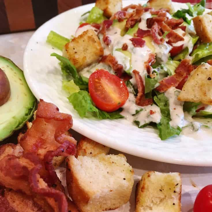 Crispy romaine lettuce, juicy grape tomatoes, crunchy-fried bacon, ripe avocado and homemade golden croutons are tossed with a creamy, tangy, fresh basil infused dressing in a hearty satisfying salad!