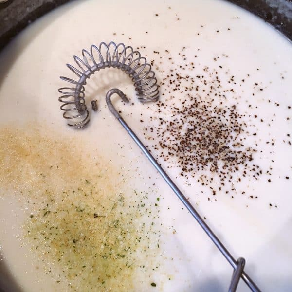 Cream sauce with seasonings being added