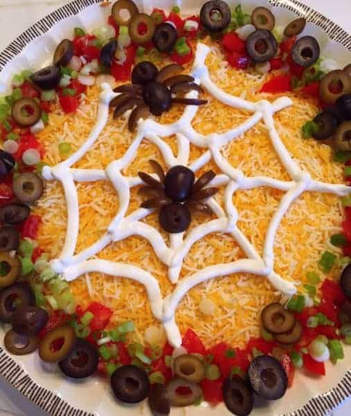Traditional Seven Layer Dip is turned into a Spooky Spider Web Halloween Dip perfect for your Halloween Parties and get together's.