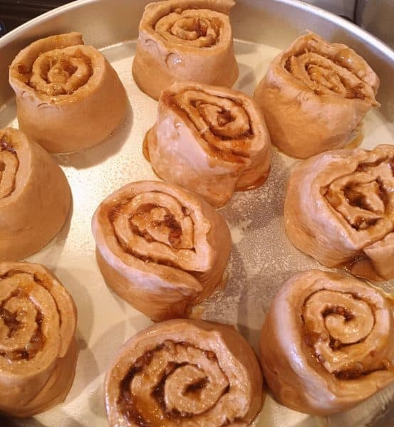 carrot cake mix cinnamon roll dough cut into 2 inch slices and placed in a prepared pan.