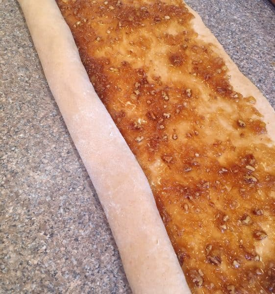 Carrot Cake mix cinnamon roll dough being rolled into long roll.