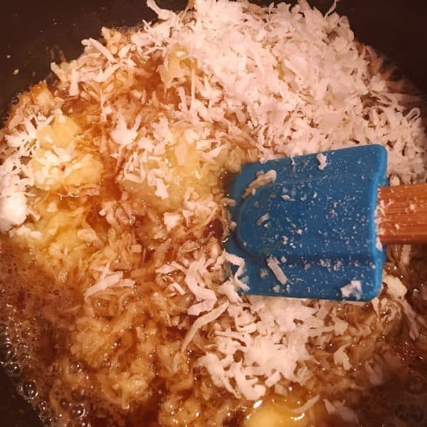Adding crushed pineapple and shredded coconut to brown sugar and butter for filling.