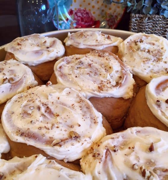 Full pan of baked carrot cake mix cinnamon rolls with frosting