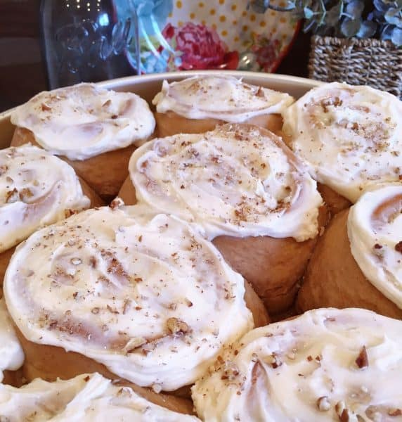 Carrot Cake Mix Cinnamon Rolls with cream cheese frosting and toasted pecans sprinkled on top.