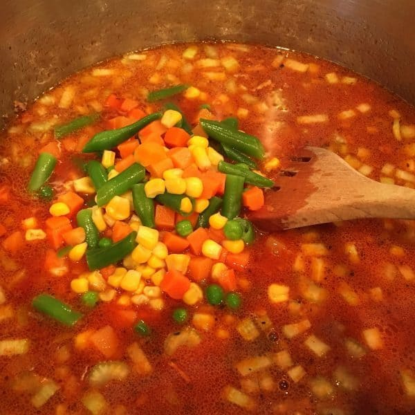 Adding a bag of vegetables to soup mix in pot