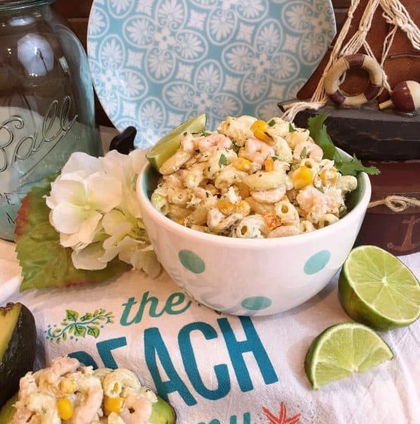 Mexican Seafood Pasta Salad on a beach towel with sliced limes.