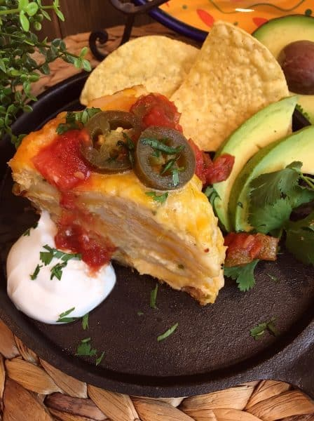 Over head shot of a thick slice of slow cooker chicken enchilada stack. Served with sour cream, salsa, jalapeno's, and tortilla chips.