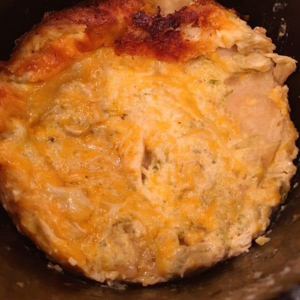 Golden melted cheese on top of baked slow cooker layered chicken enchilada casserole. Crispy golden top.