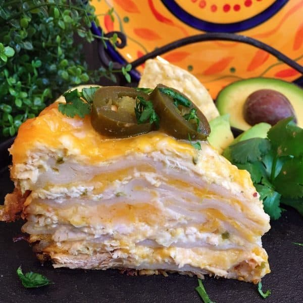 Slice of Layered Slow Cooker Chicken Enchilada Casserole. Topped off with sliced jalapeno's.