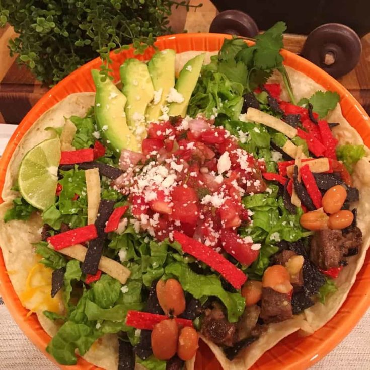 This Steak Fajita Taco Salad is loaded with seasoned beef, cilantro lime rice, spicy pinto beans, all on top of a cheesy flour tortilla and topped with all the delicious veggies needed to make a great salad.