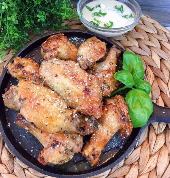 Air Fryer Garlic Parmesan Wings on Cast Iron skillet with dipping sauce.