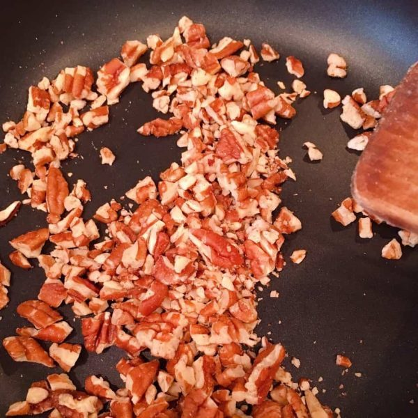 Chopped pecans in skillet over medium heat. Toasting.