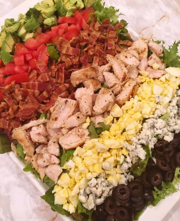 Leafy greens topped with grilled chicken, hard boiled eggs, crumbled blue cheese, bacon, tomatoes, olives, and avocados combine to create a delicious light and tasty meal.