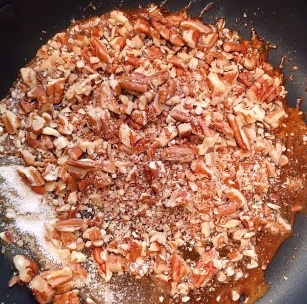 Adding chopped pecans to the caramelized sugar.