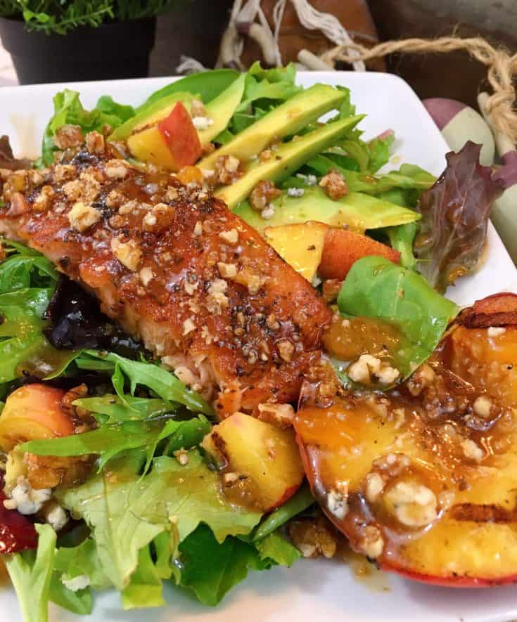 Perfectly grilled Salmon on a bed of spring mix greens with grilled peaches, avocado, candied pecans, and blue cheese drizzled with a scrumptious balsamic peach dressing.