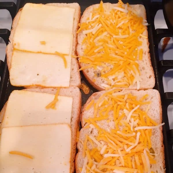 Sourdough bread on a hot grill with slices of cheese.