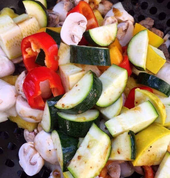 Vegetables with grilled meats in grilling basket on hot BBQ