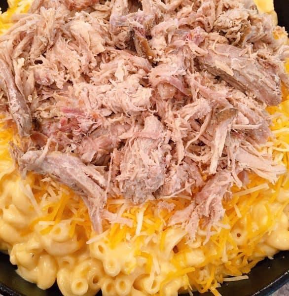 Adding shredded pork on top of macaroni and cheese