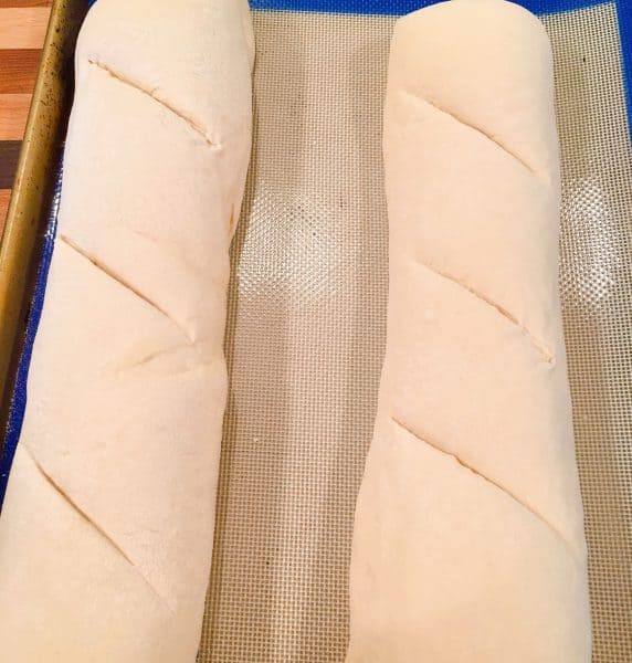 Cutting long slits into each loaf of bread.