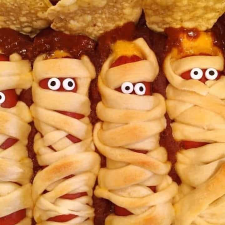 hot dogs wrapped in crescent dough strips and laid to rest in a bed of chili