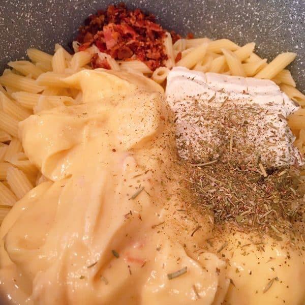 Adding bacon and Italian seasonings to pasta mixture