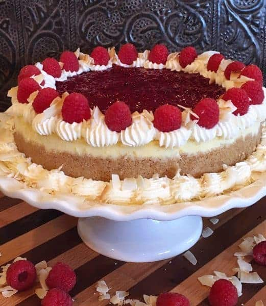 Rich Creamy Coconut Cheesecake is swirled with Raspberry Cheesecake and topped off with a fresh raspberry sauce, whipped cream, fresh raspberries and large toasted coconut flakes. It's the most spectacular cheesecake EVER!