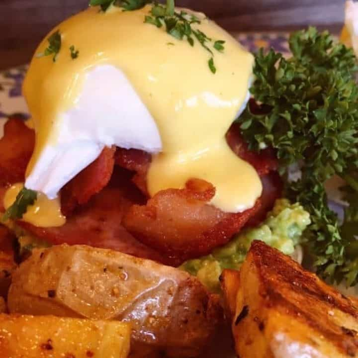Eggs Benedict on a plate with potatoes