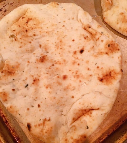 slice of naan bread on baking sheet