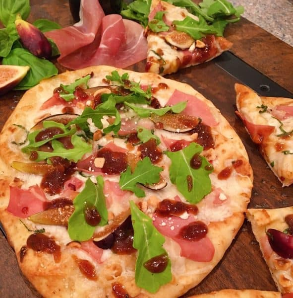 Fig Prosciutto Hazelnut Pizza on a board with props