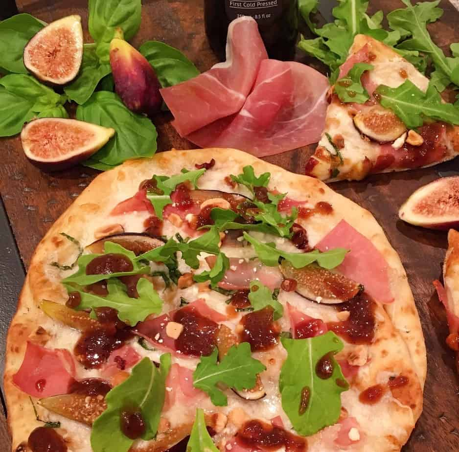 Whole Fig and Prosciutto Pizza on a board with figs and basil and cut slices of pizza