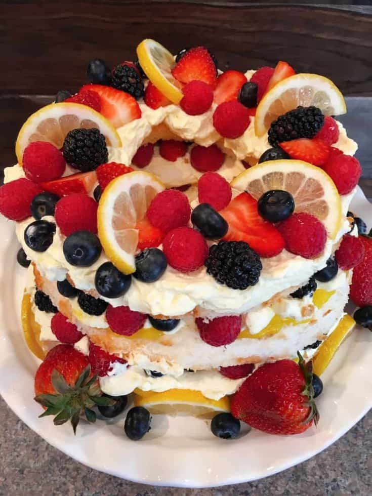 Flavorful light and airy angel food cake is layered with lemon pudding, lemon cream,and lots of fresh berries for this perfect Easy Spring Time dessert!