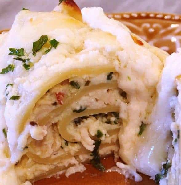 Lasagna noodles are rolled up with a creamy cheese, spinach, and chicken filling and topped with a thick creamy Alfredo sauce for one amazingly delicious pasta dish.