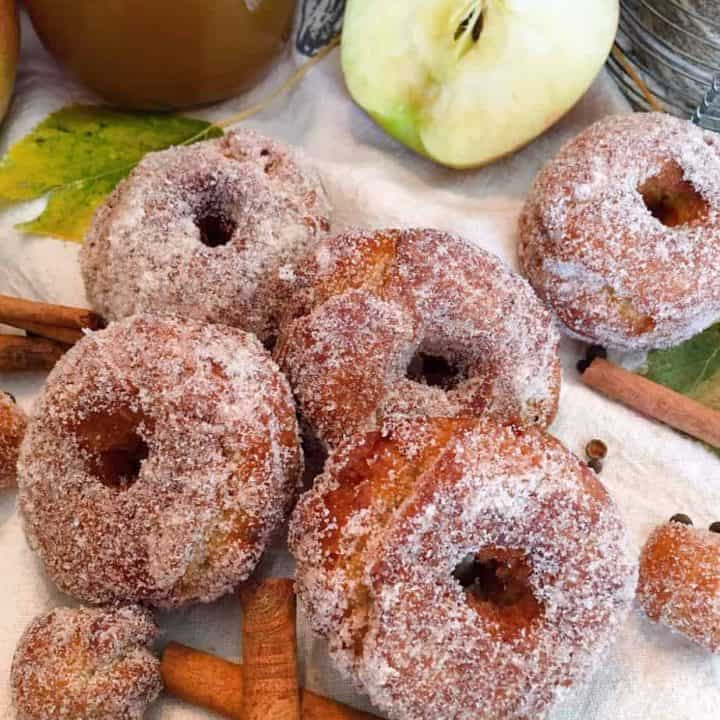 Group of Apple Cider Donuts with cinnamon sticks and apples