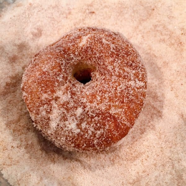 Apple Cider Donuts being rolled in cinnamon sugar