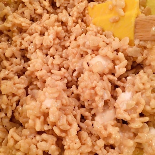 Stirring melted marshmallow mixture into rice krispies