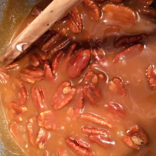 Pecan Halves being stirred into brown sugar mixture.