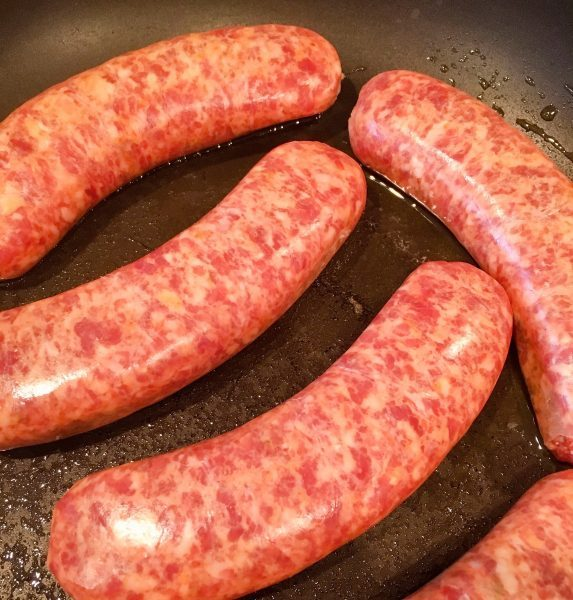 Italian Sausage in a skillet with olive oil