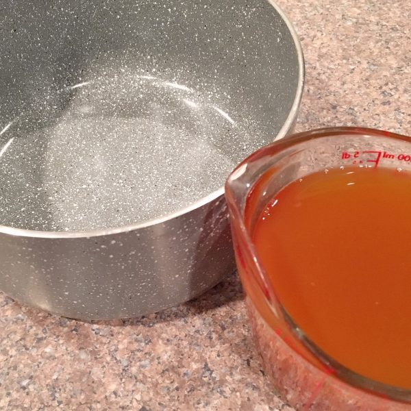 two cups of apple cider in a sauce pan