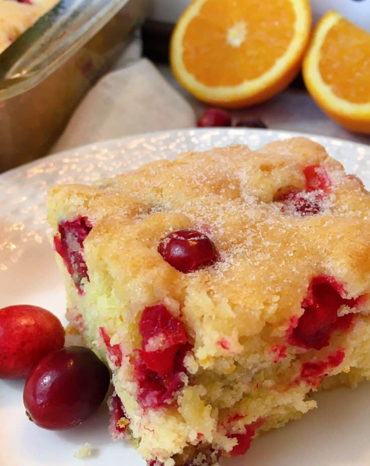 Cranberry Orange Buttermilk Coffee Cake is made with fresh Orange zest, orange juice, and tangy seasonal fresh cranberries in a delicious moist buttermilk batter topped with a sprinkle of sparkling sugar. It's the perfect Holiday breakfast dish!