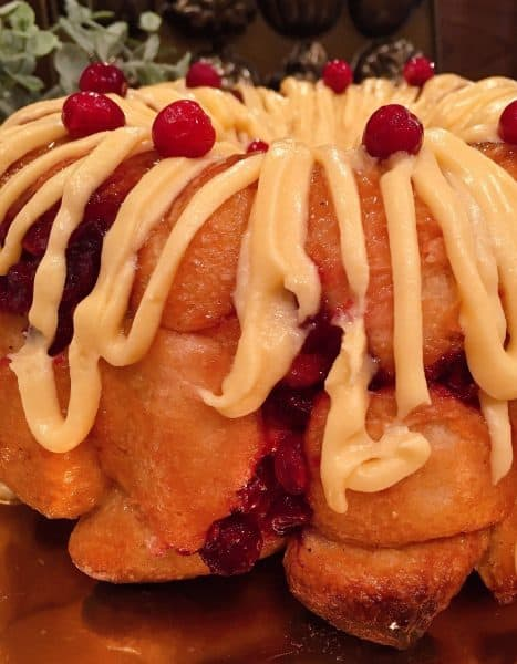 Drizzle of orange cream cheese frosting over monkey bread