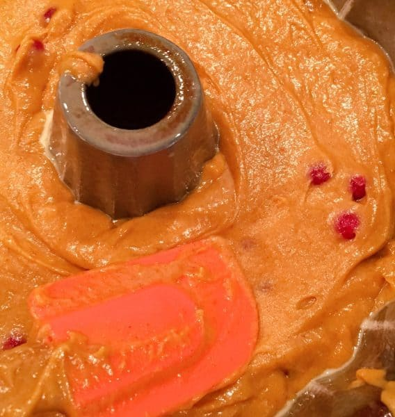 Spreading cake batter in prepared bundt pan
