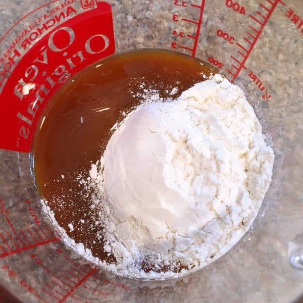 Caramel sauce and flour in glass measuring cup