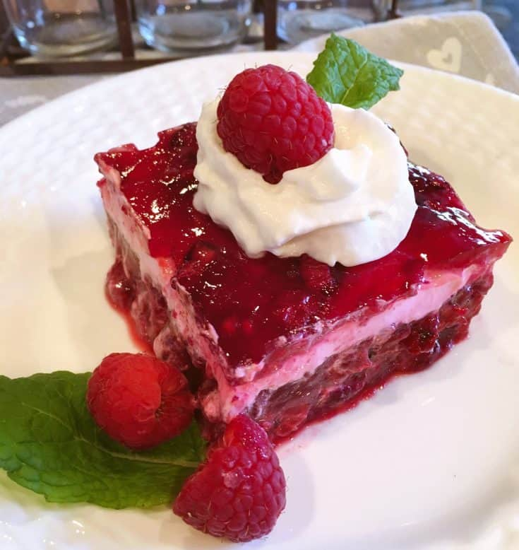 Raspberry Layered Jello Salad has a base of frozen raspberries, pineapple, and fresh bananas topped with layer of sour cream, and topped off with another thin layer of raspberries and jello! It's the perfect side salad for Holidays and Special Occasions.