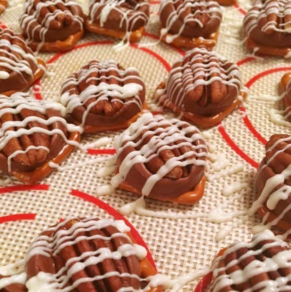 Drizzling white chocolate over pecans