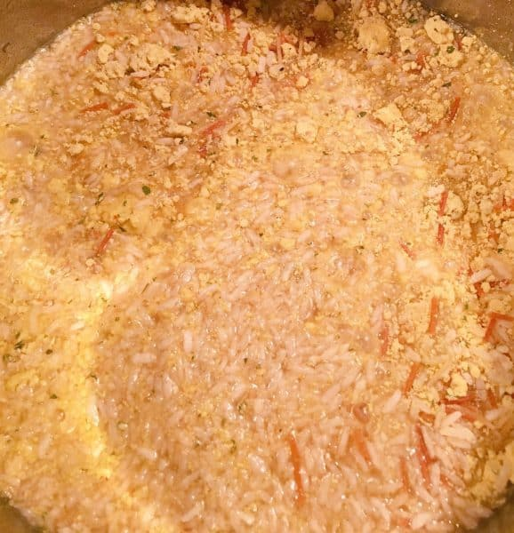 adding chicken broth to rice mixture