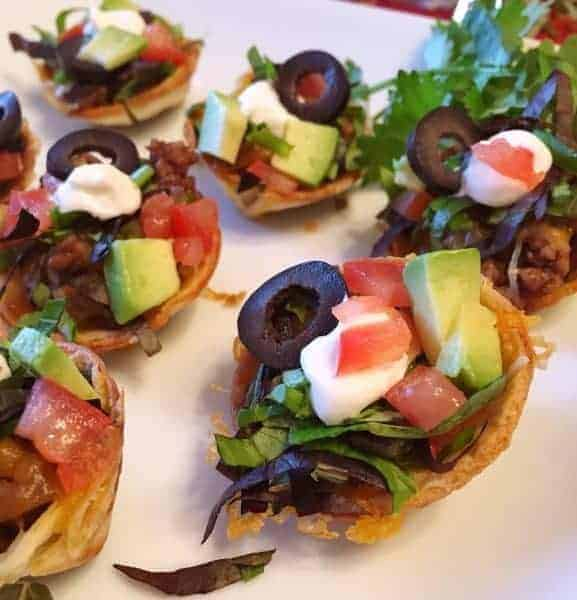 Mini Tostada Bites are the perfect Mexican Appetizer! Homemade flour tortilla cups are filled with beans, ground beef, cheese, lettuce, sour cream, and more! A great party and game day treat!