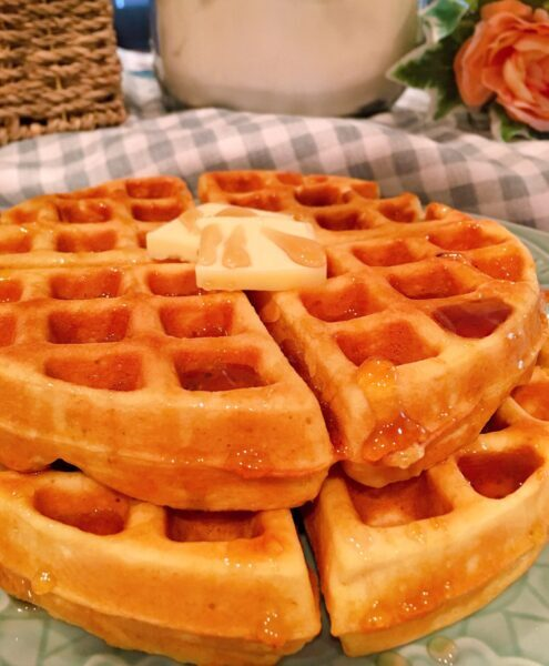 waffles stacked on a plate with butter