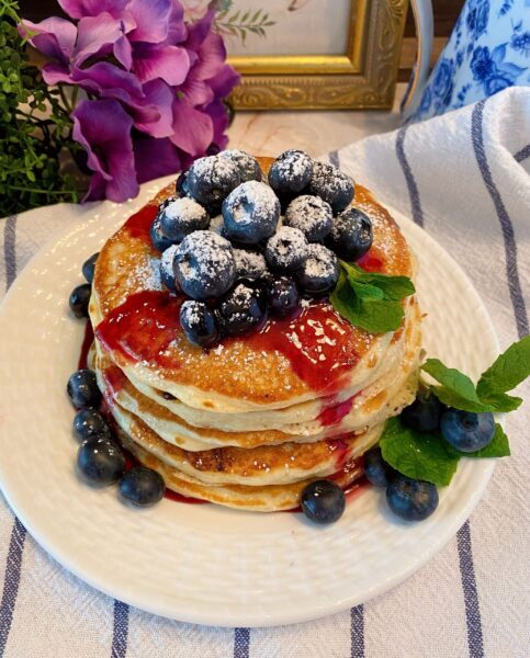 Blueberry Buttermilk Pancakes in a stack with syrup and fresh blueberries