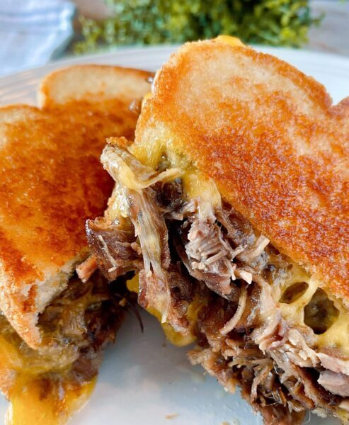 Roast beef grilled cheese sandwich cut in half and ready to eat