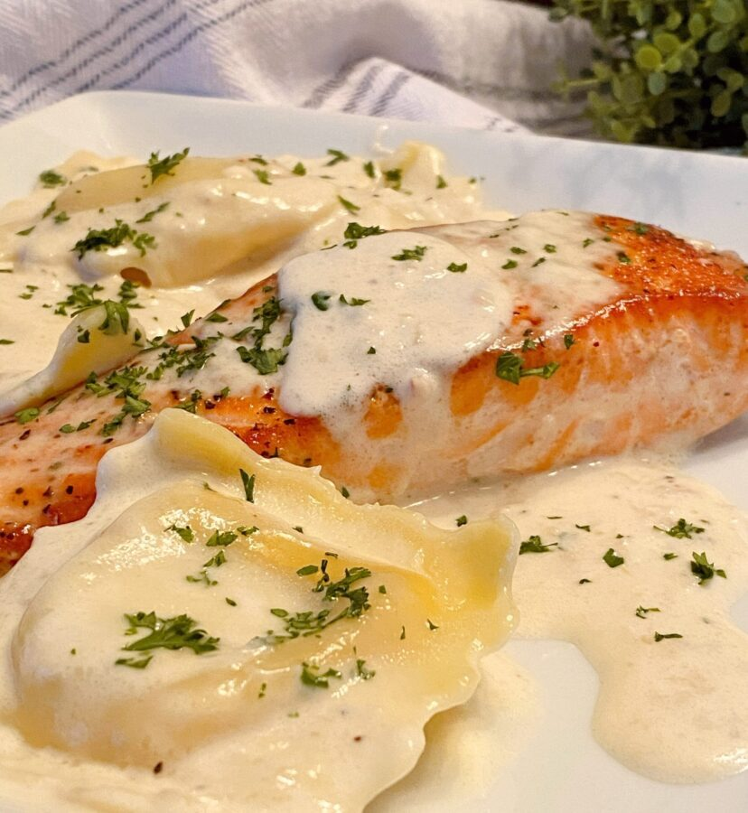 Salmon with Creamy Tuscan Sauce and lobster ravioli on a plate.